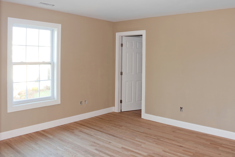 Newly constructed house interior room with unfinished wood floors window and closet door. Electrical connections are partially unfinished.